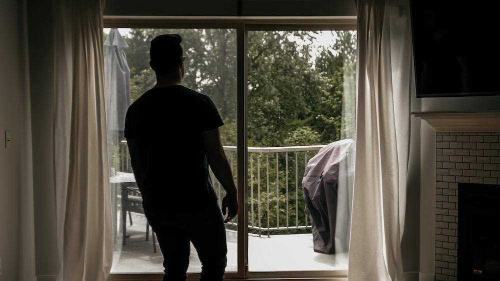 man in black t-shirt standing near window