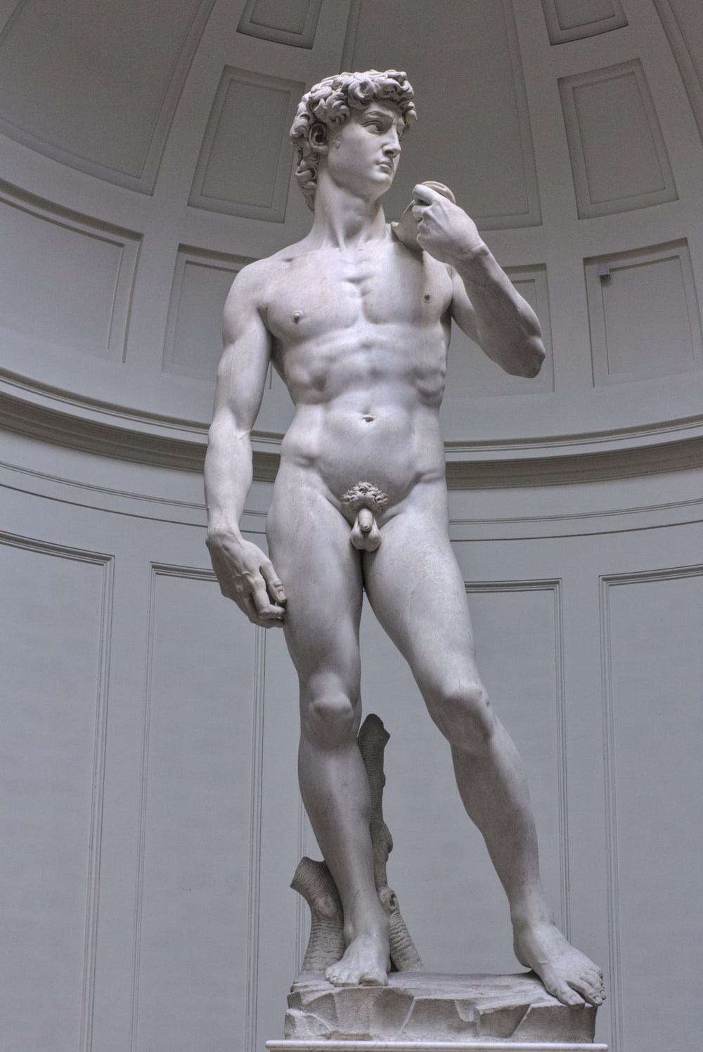naked man statue near white wooden wall