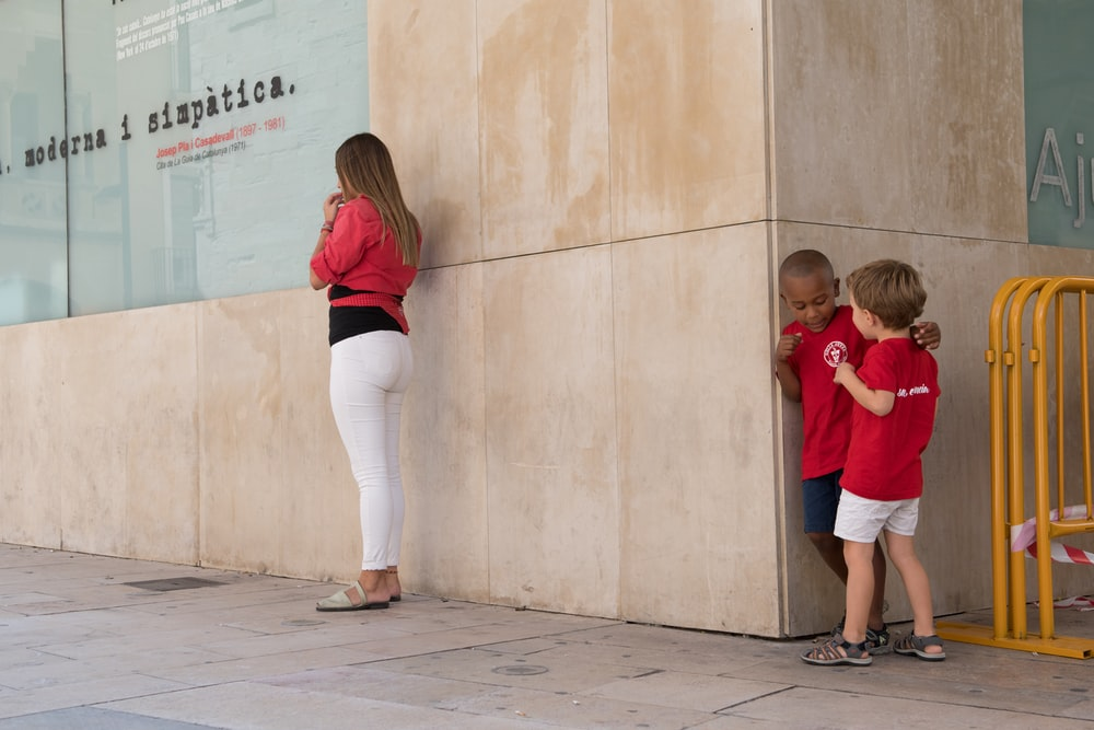 woman in red shirt and white pants standing beside boy in red shirt