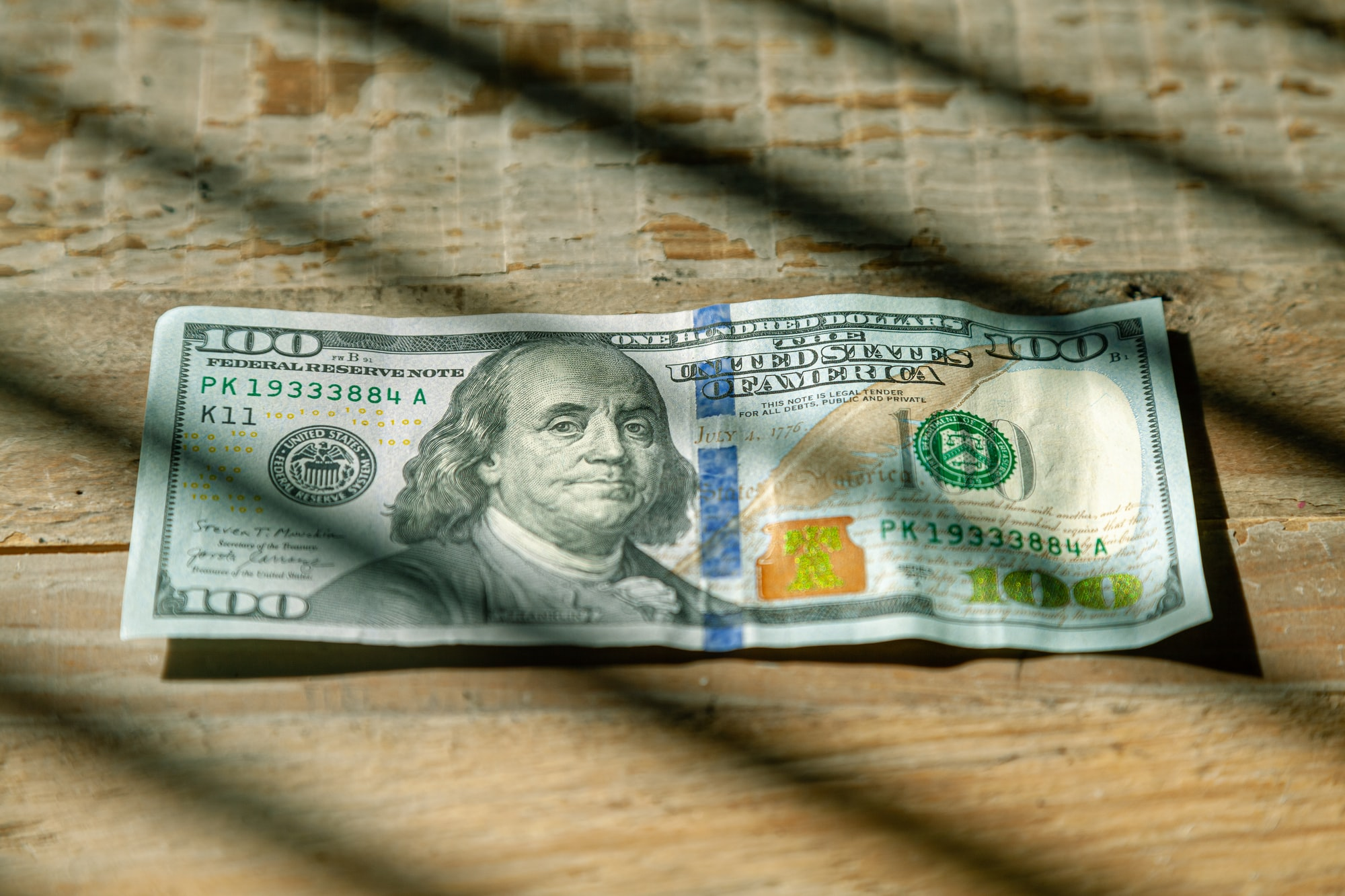 US Currency One hundred dollar bill flat lay on wood background