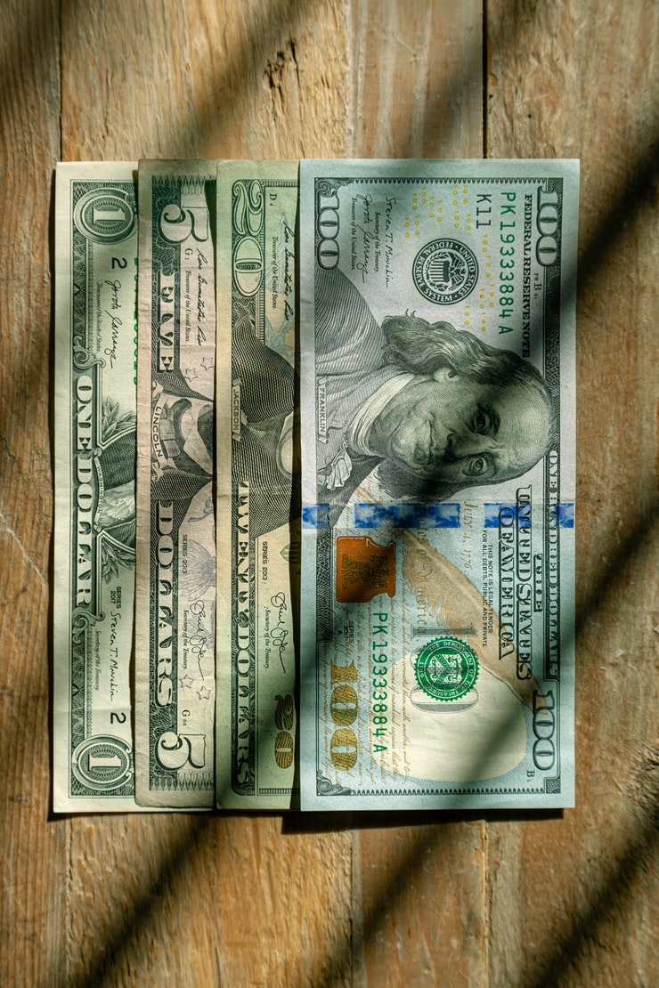US Currency $100, $20, $5, $1 denominations flat lay on wood background