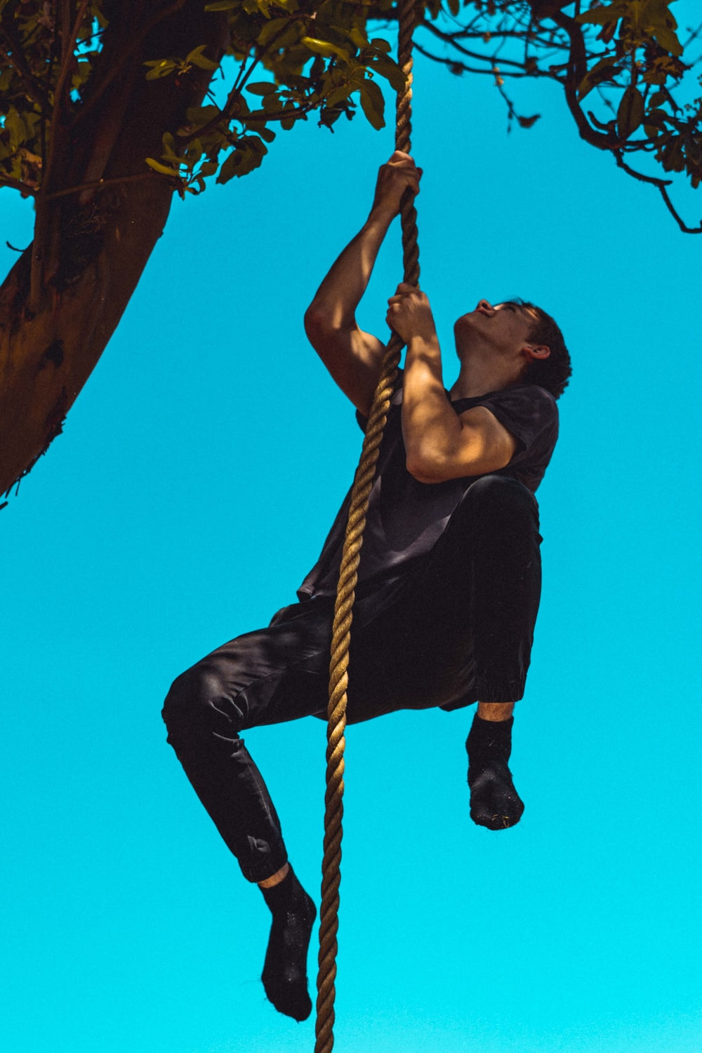 man in black tank top and black pants climbing on brown rope