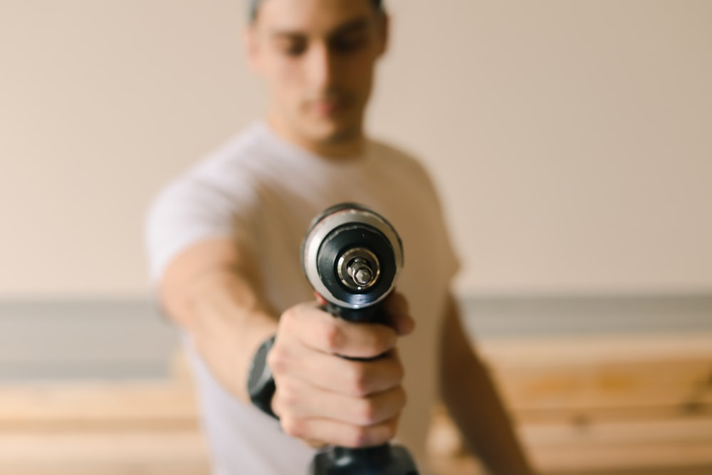 man in white crew neck t-shirt holding black and silver dumbbell