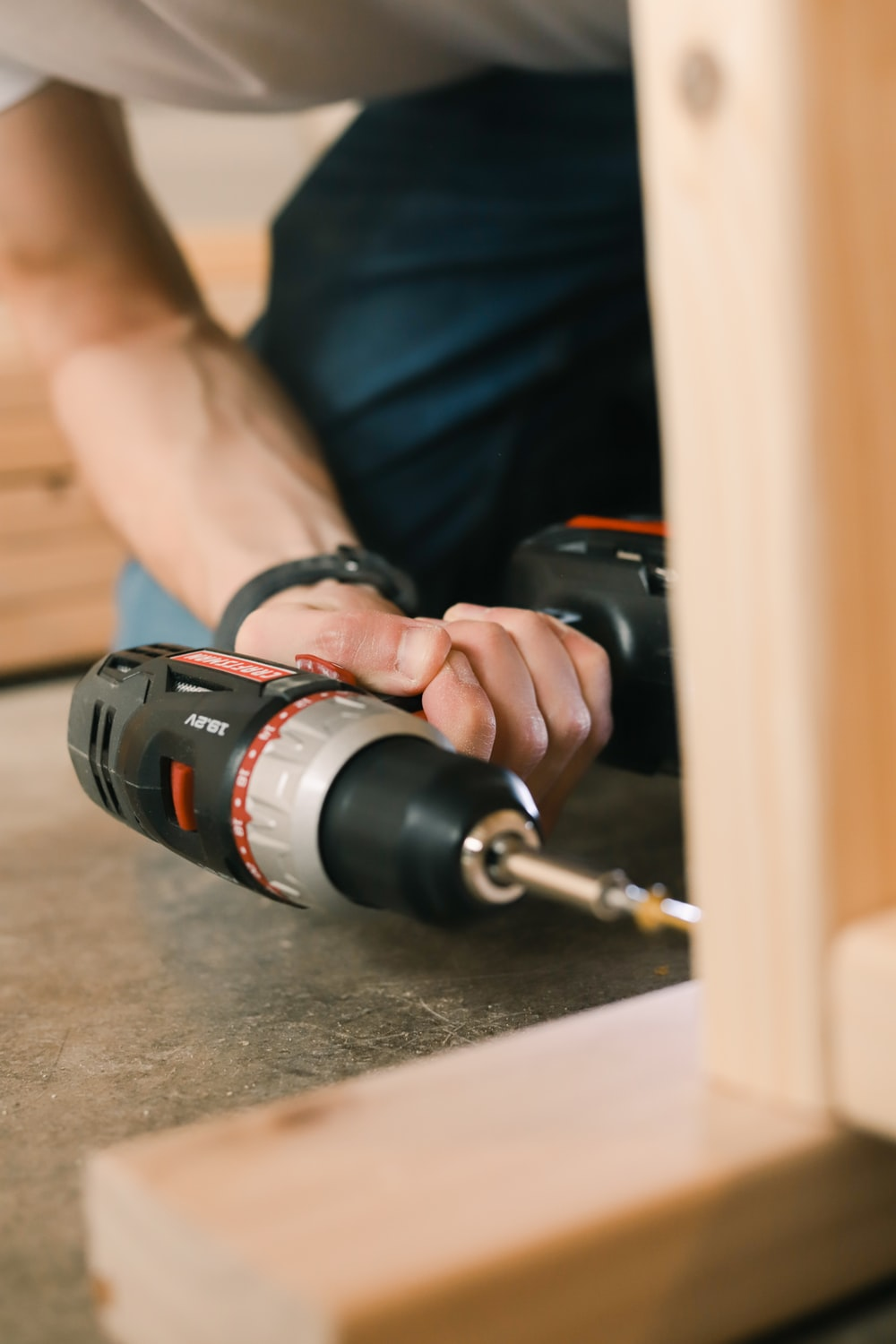 person holding black and red cordless hand drill