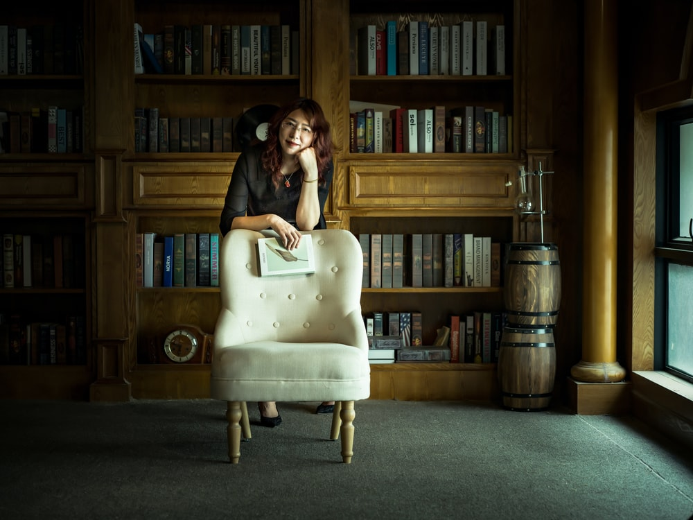woman in black long sleeve shirt sitting on white chair