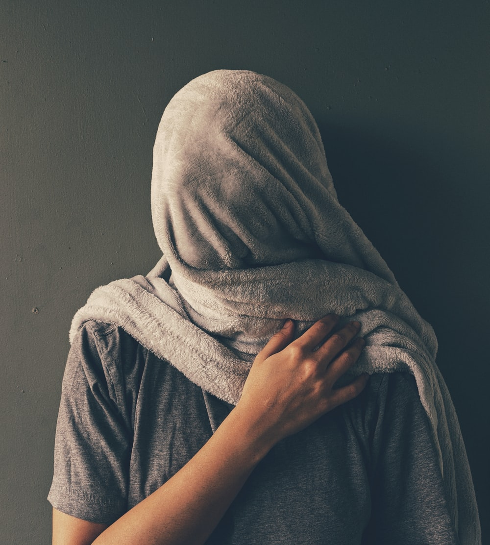 person in gray hijab covering face