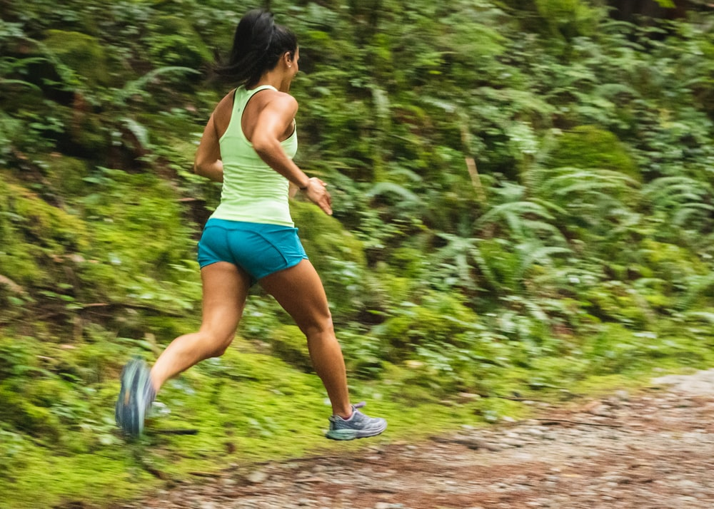 woman in white tank top running on dirt road during daytime
