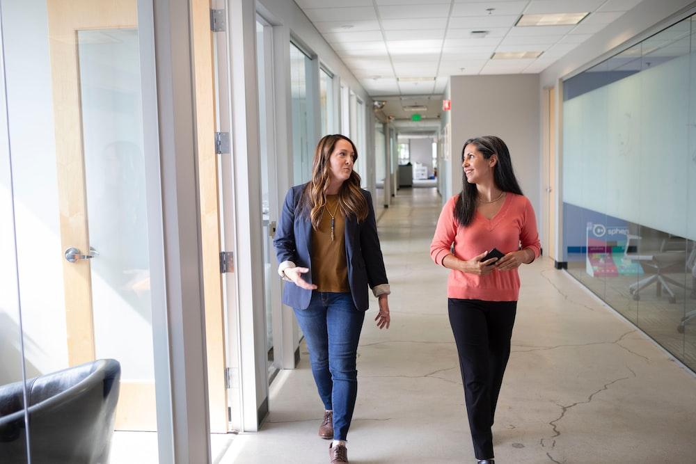 2 women standing near white wall