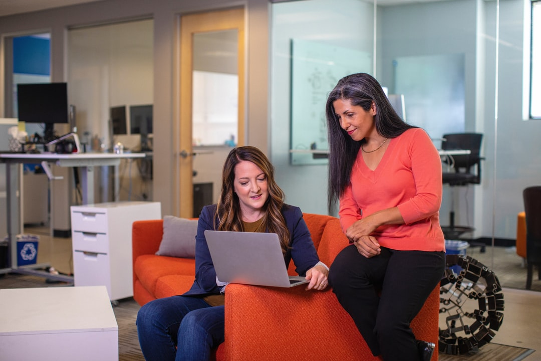 Two business women talking sales on a sofa with laptop