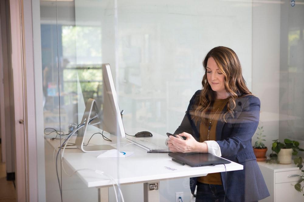 woman in black leather jacket using macbook air