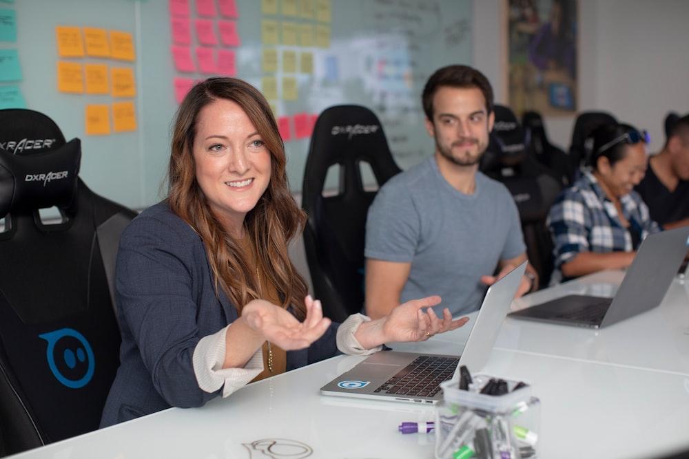 woman in black long sleeve shirt sitting beside man in gray crew neck shirt