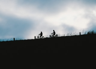 silhouette of people riding motorcycle during daytime