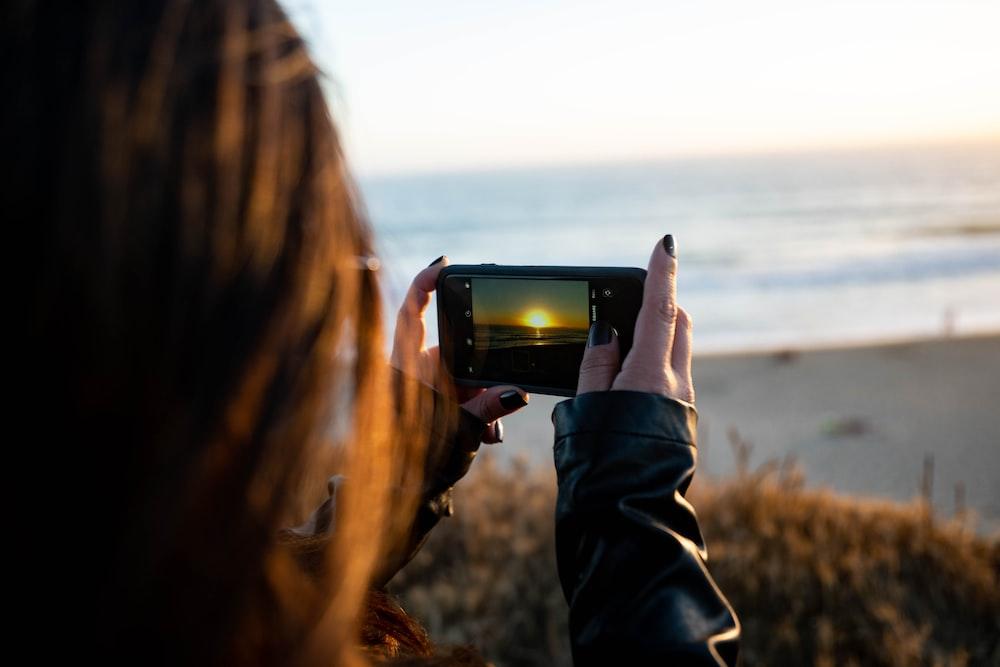 woman taking photo of sea during daytime