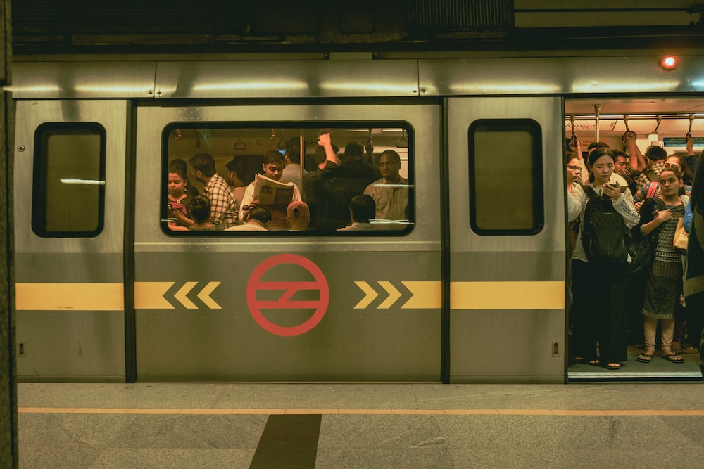 man in black jacket sitting beside yellow and red train