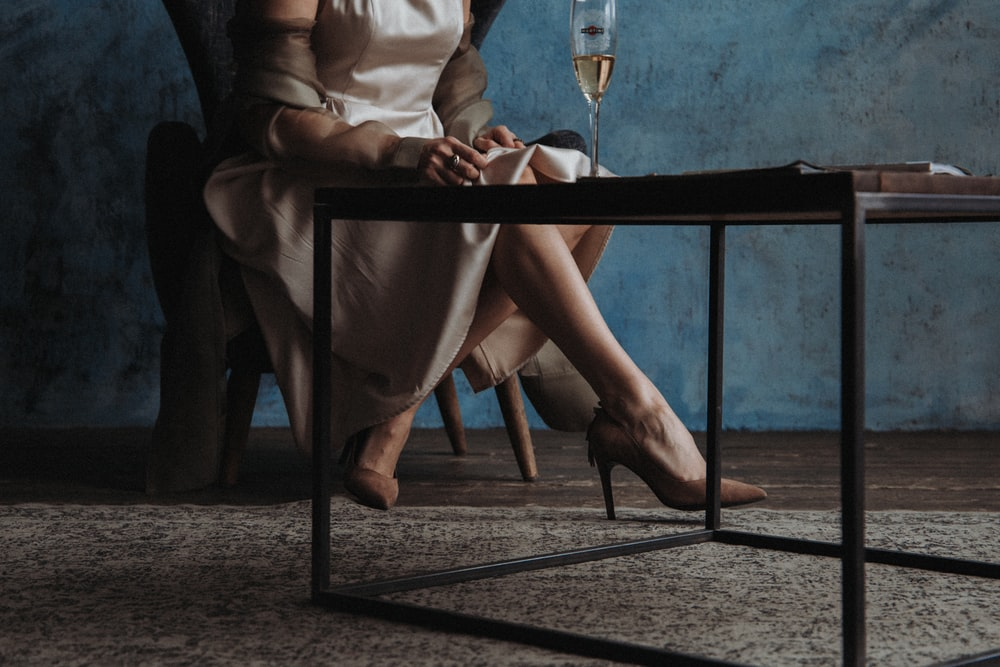 woman in white long sleeve shirt sitting on chair holding wine glass