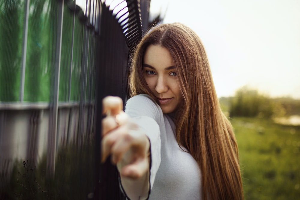 woman in white long sleeve shirt standing near green metal fence during daytime