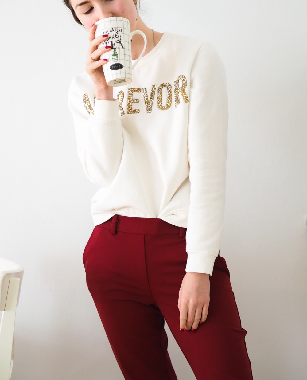woman in white long sleeve shirt and red pants holding white ceramic mug
