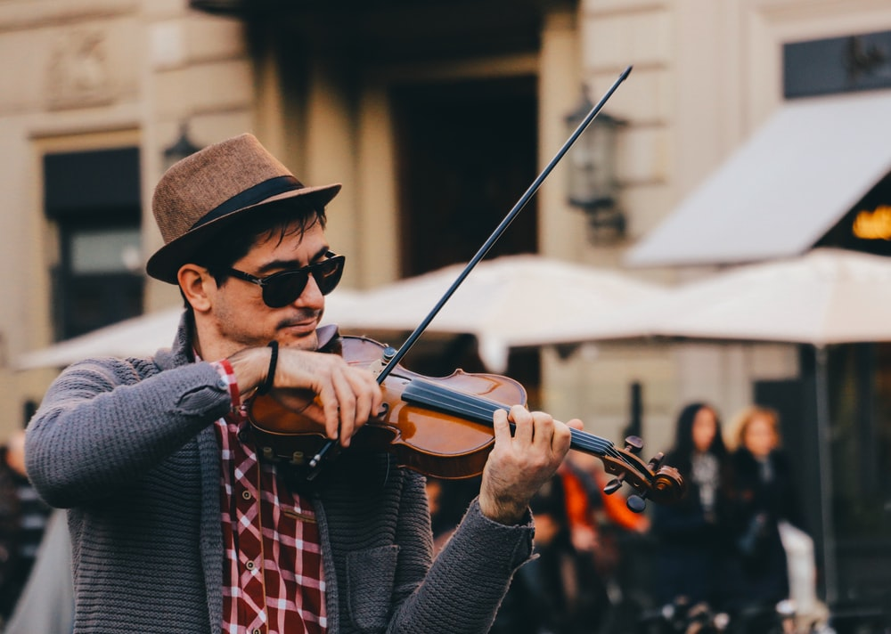 man in black and white long sleeve shirt playing violin