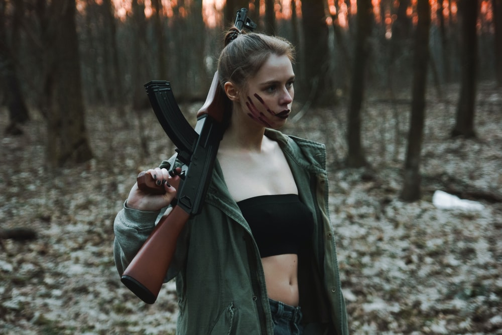 woman in black leather jacket holding black rifle