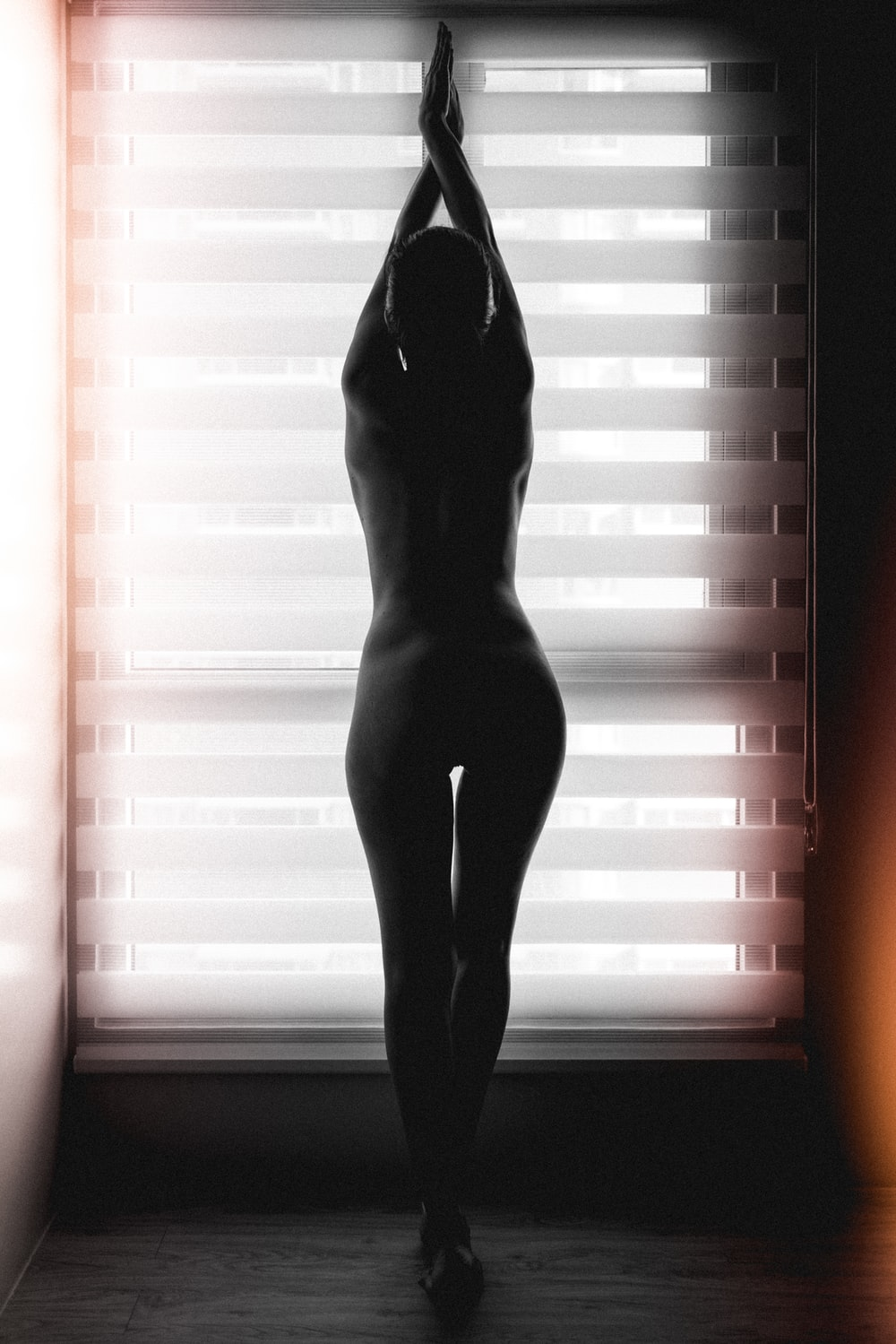 woman in black stockings standing by the window