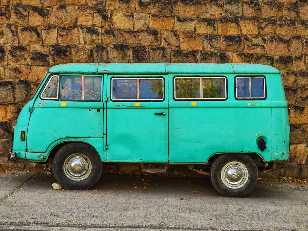 teal and white volkswagen t-2 parked beside brown brick wall