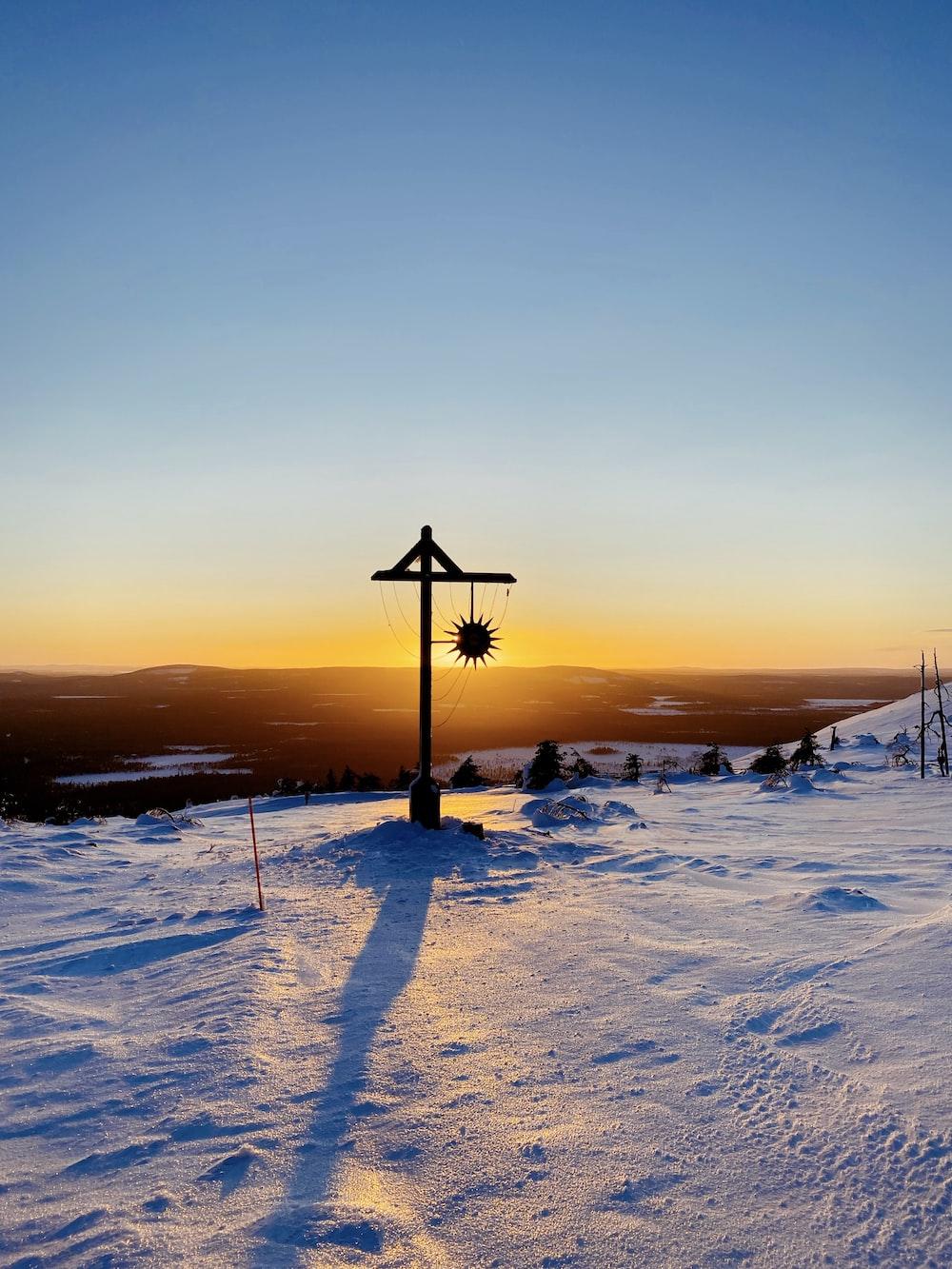 black street light on snow covered ground during sunset