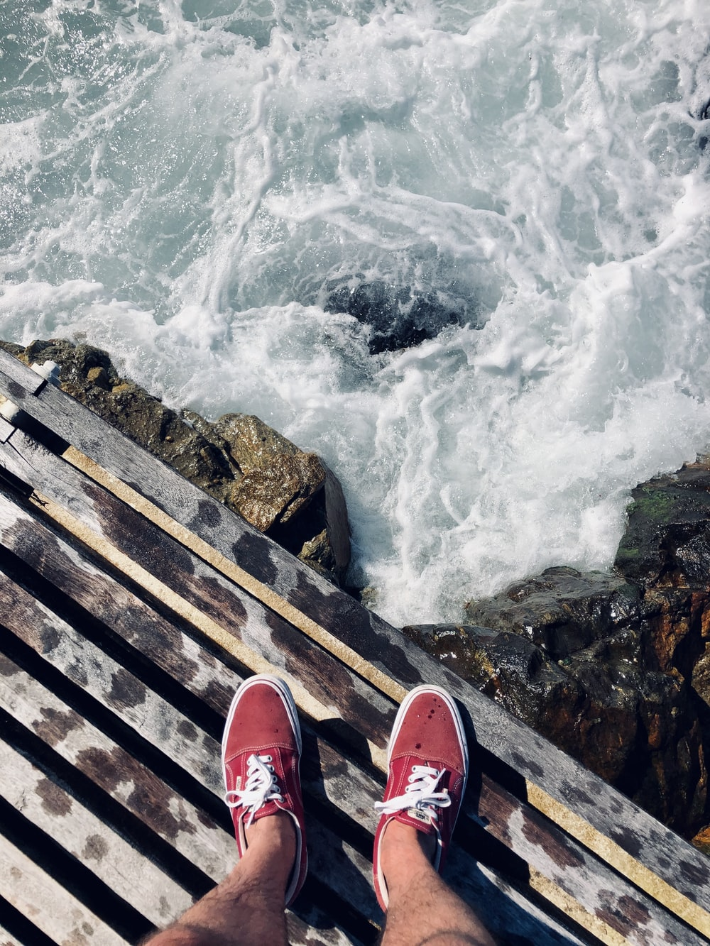 person in red and white sneakers standing on wooden dock over the water