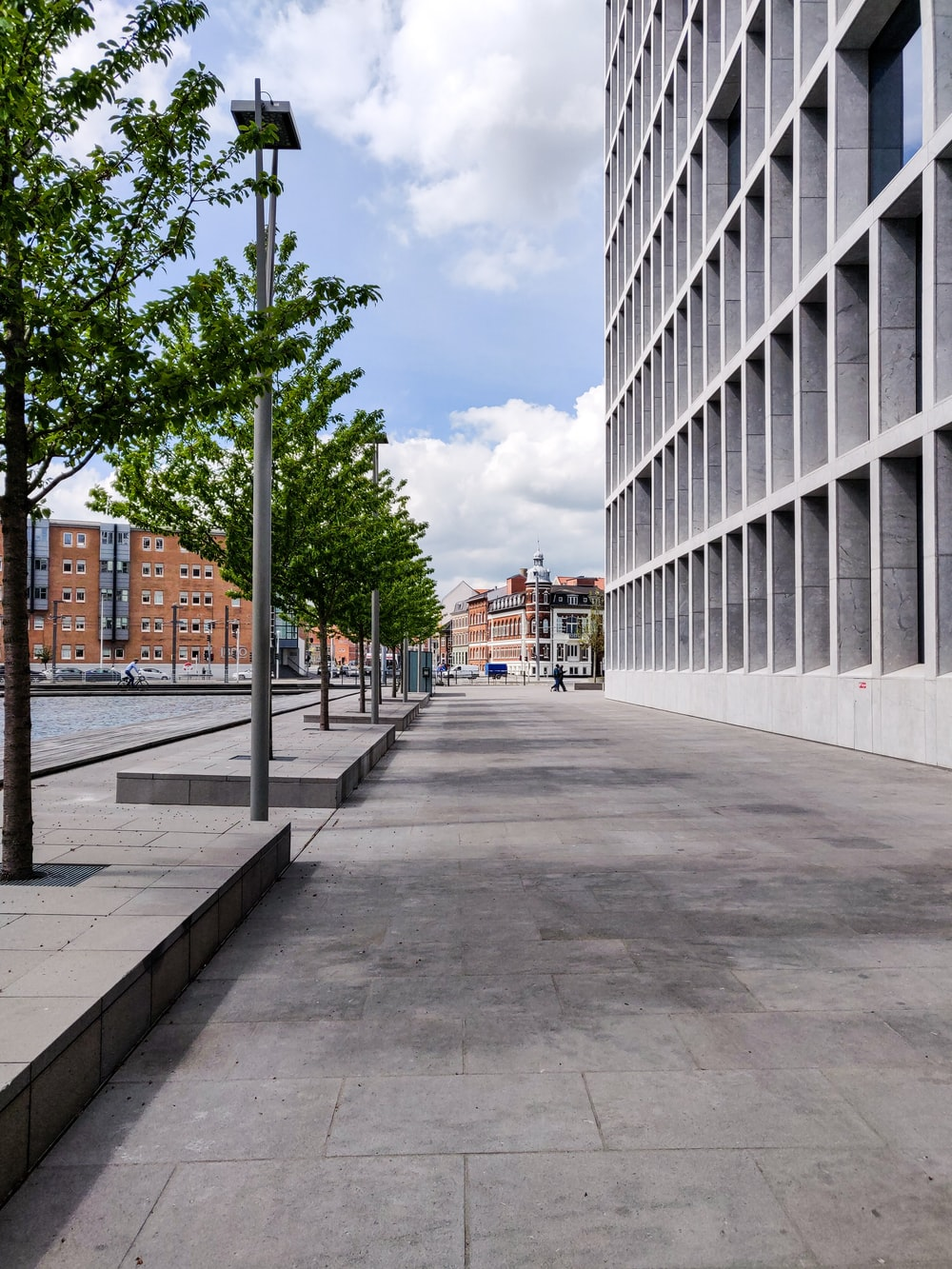 gray concrete road between white concrete buildings during daytime