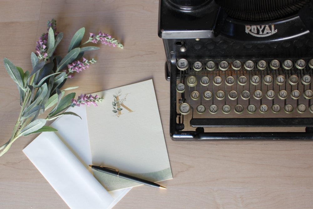 white printer paper on black typewriter