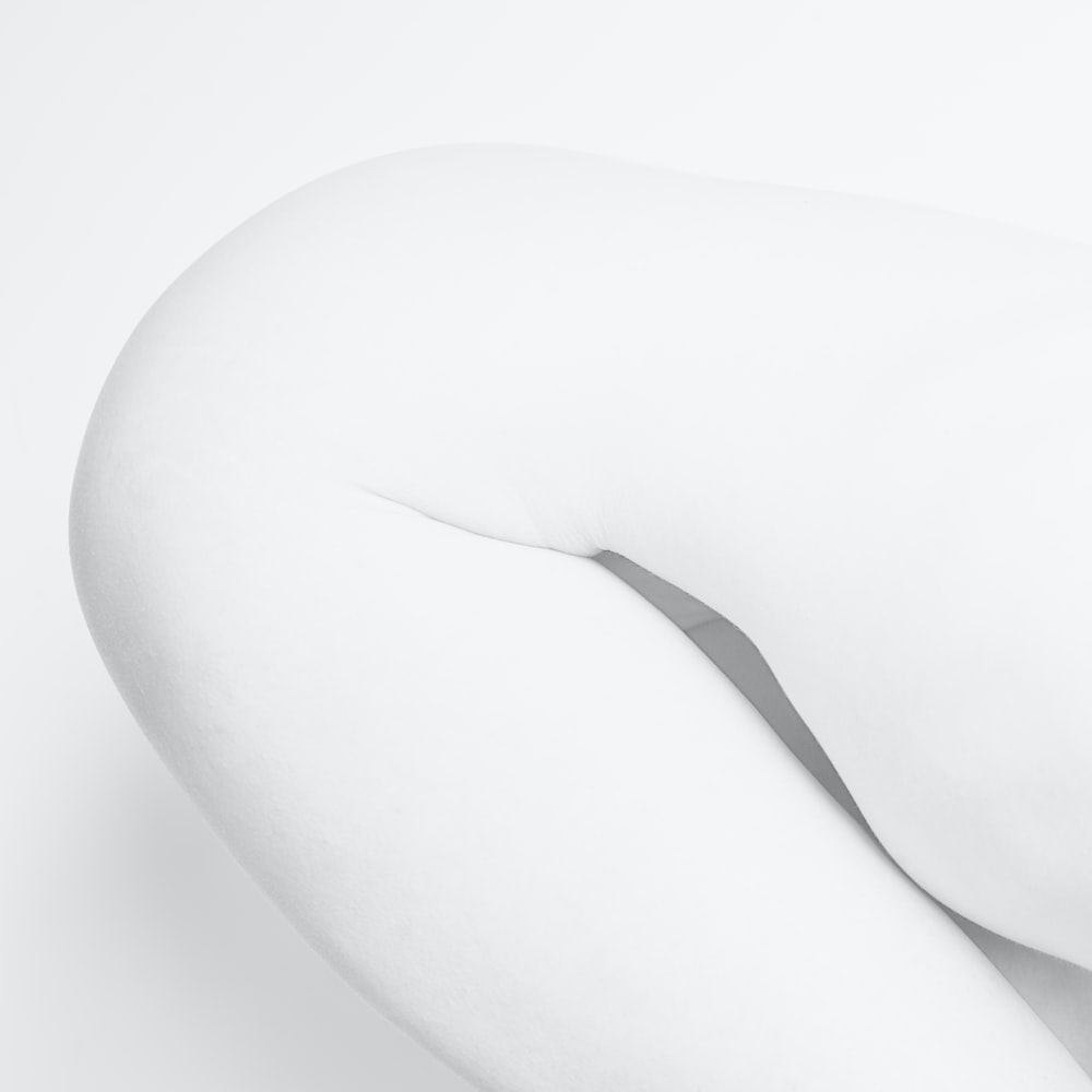 woman in white stockings lying on white surface