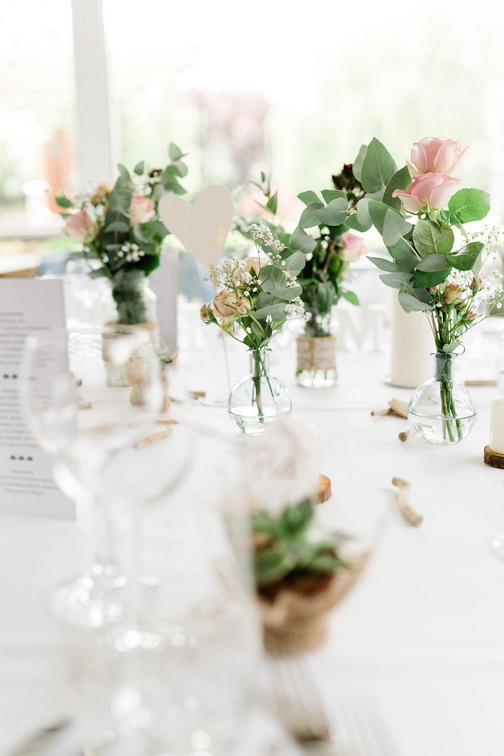 pink and white roses in clear glass vase on table