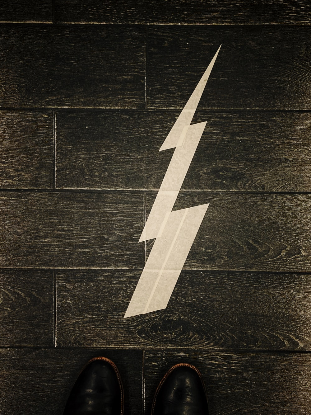 white arrow pointing at brown wooden wall