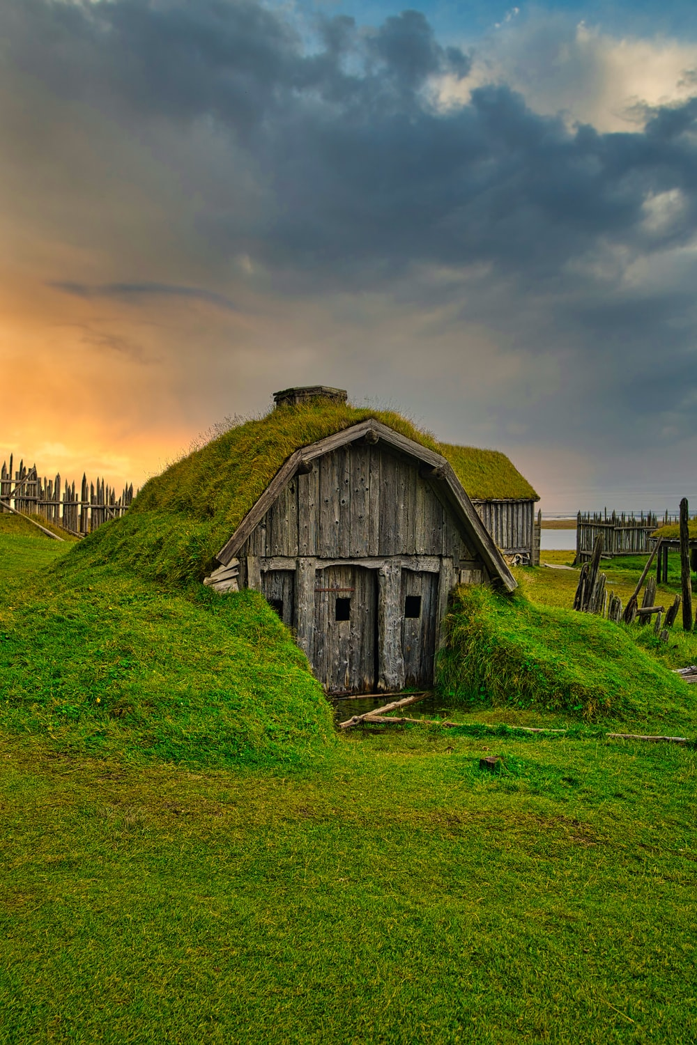 brown wooden house on green grass field during sunset