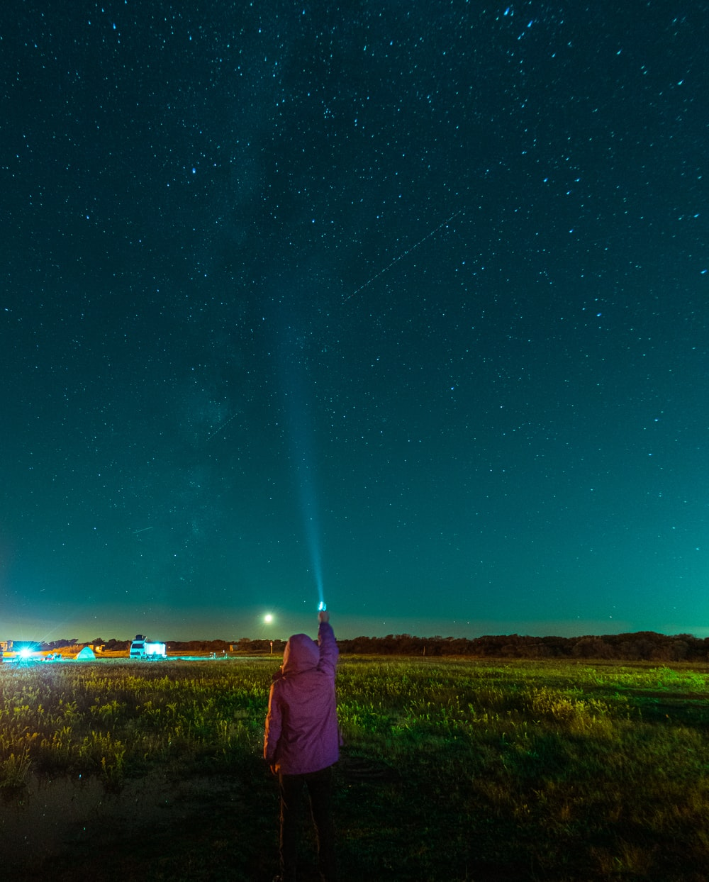 woman in purple jacket standing on green grass field during night time