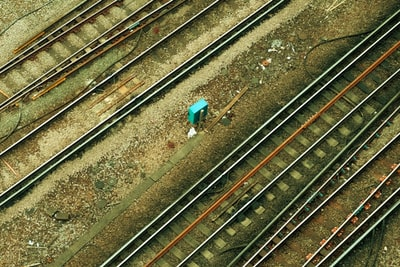 Croydon person in blue jacket standing on train rail