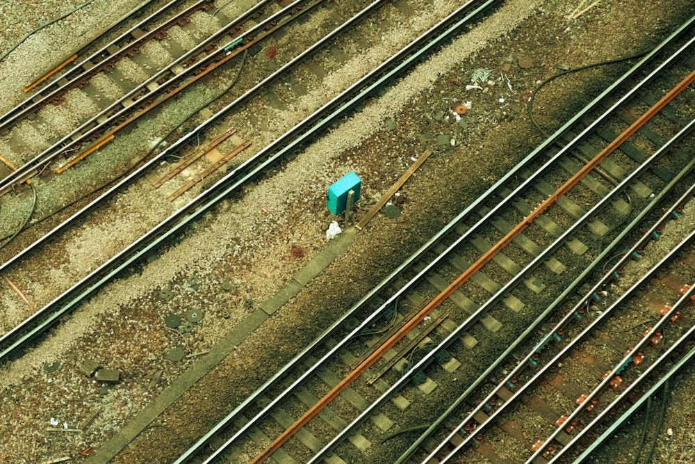 person in blue jacket standing on train rail