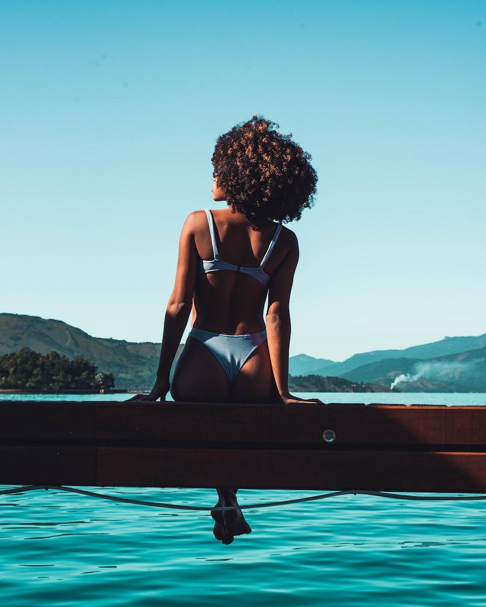 woman in black bikini sitting on black wooden bench during daytime