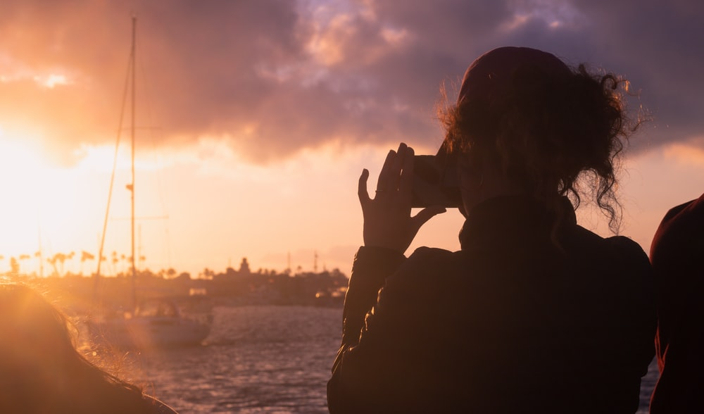 silhouette of person covering face with hands during sunset