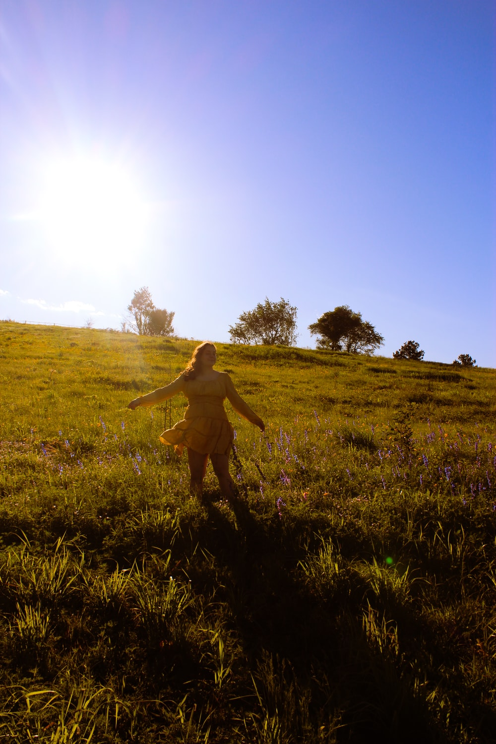 woman in brown dress walking on green grass field during daytime