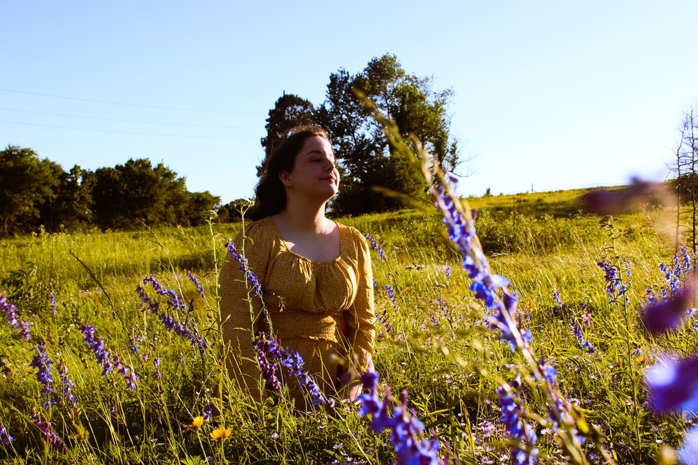 woman in yellow shirt standing on green grass field during daytime