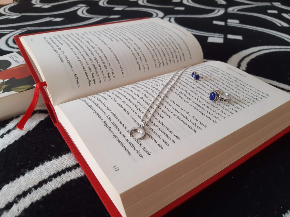 silver and gold necklace on book page