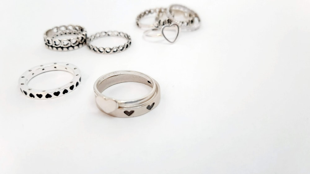 silver and diamond ring on white surface