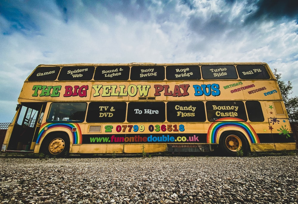 yellow red and blue bus on gray sand during daytime