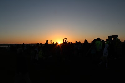people standing on field during sunset solstice teams background