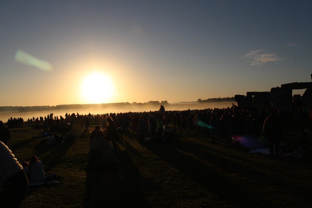 people standing on field during sunset