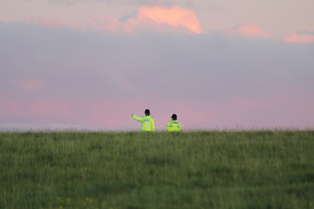 2 person sitting on green grass field during sunset
