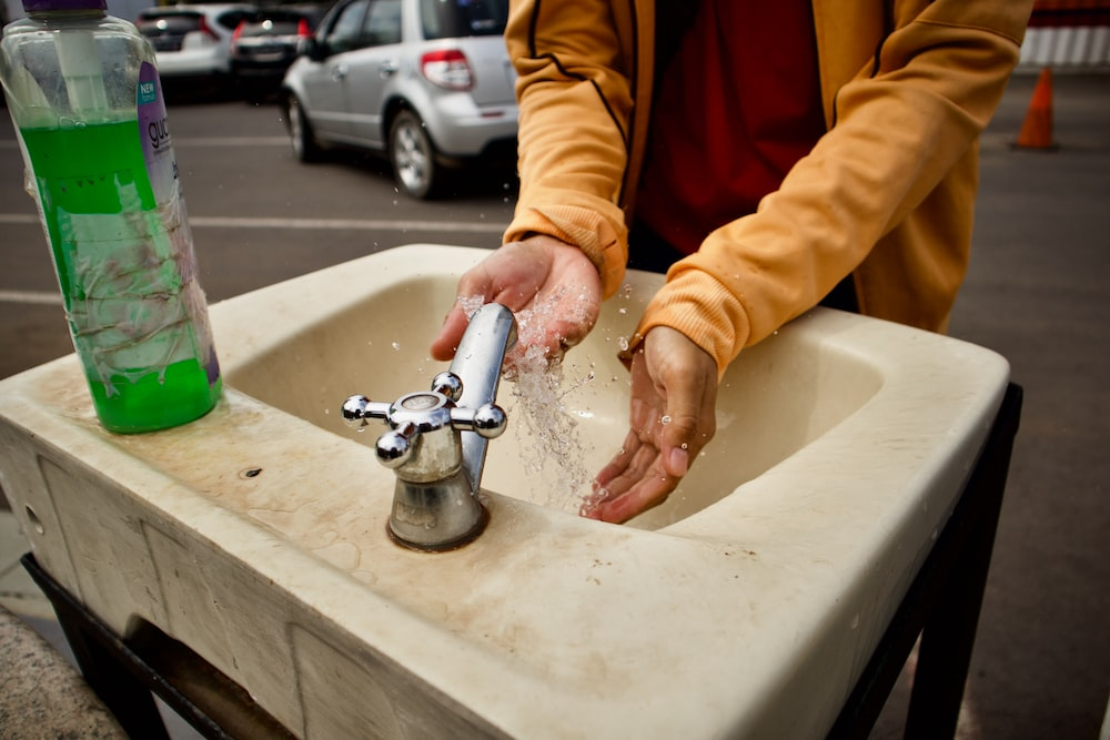 person in orange jacket washing hand