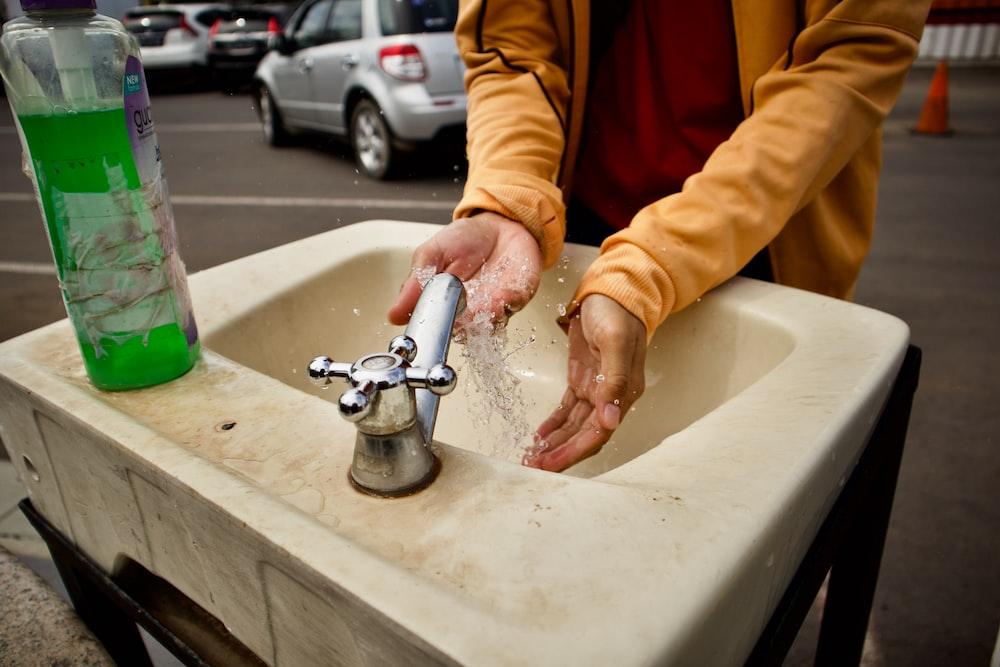 person in orange jacket washing hand