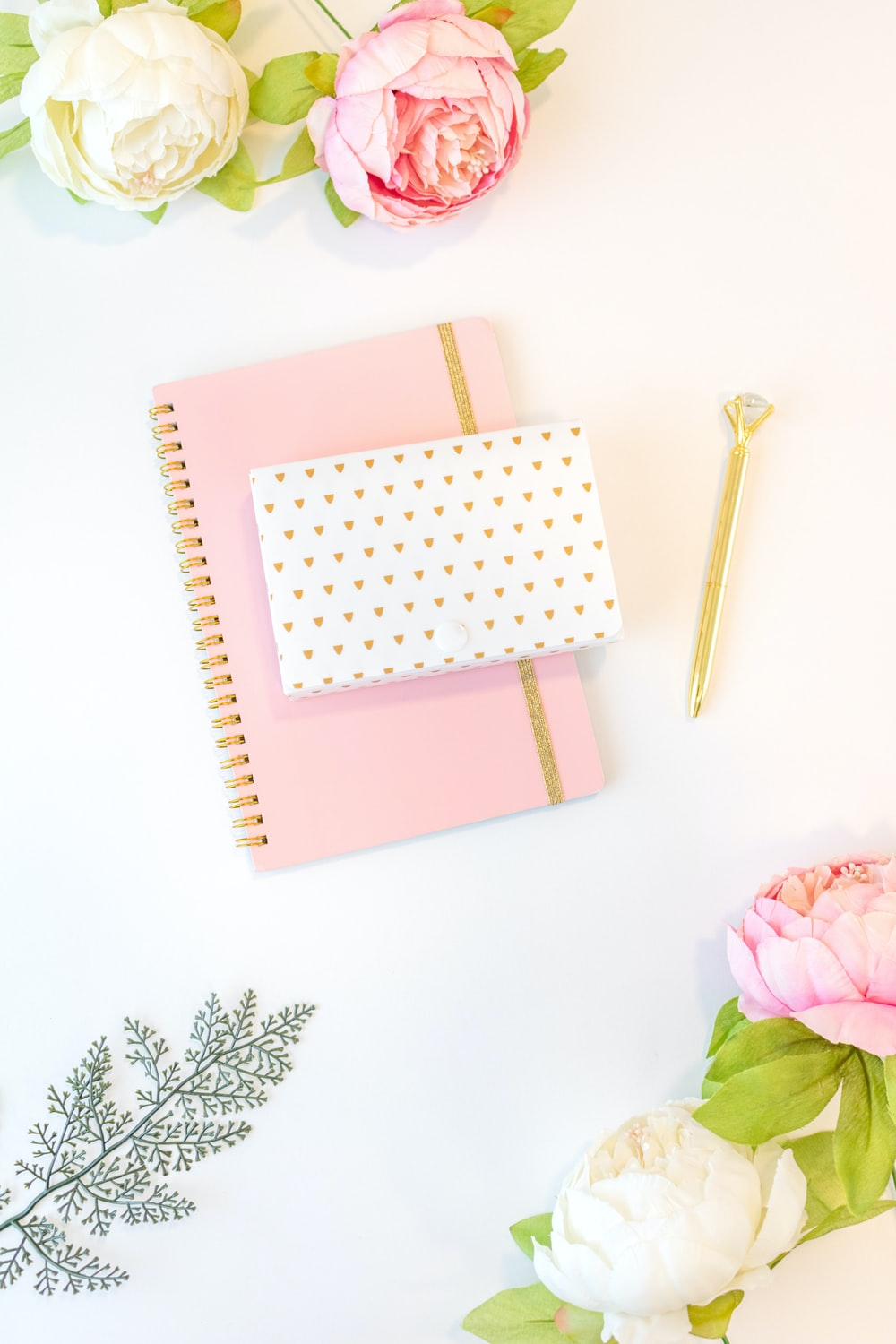 pink and white book on white and green floral textile