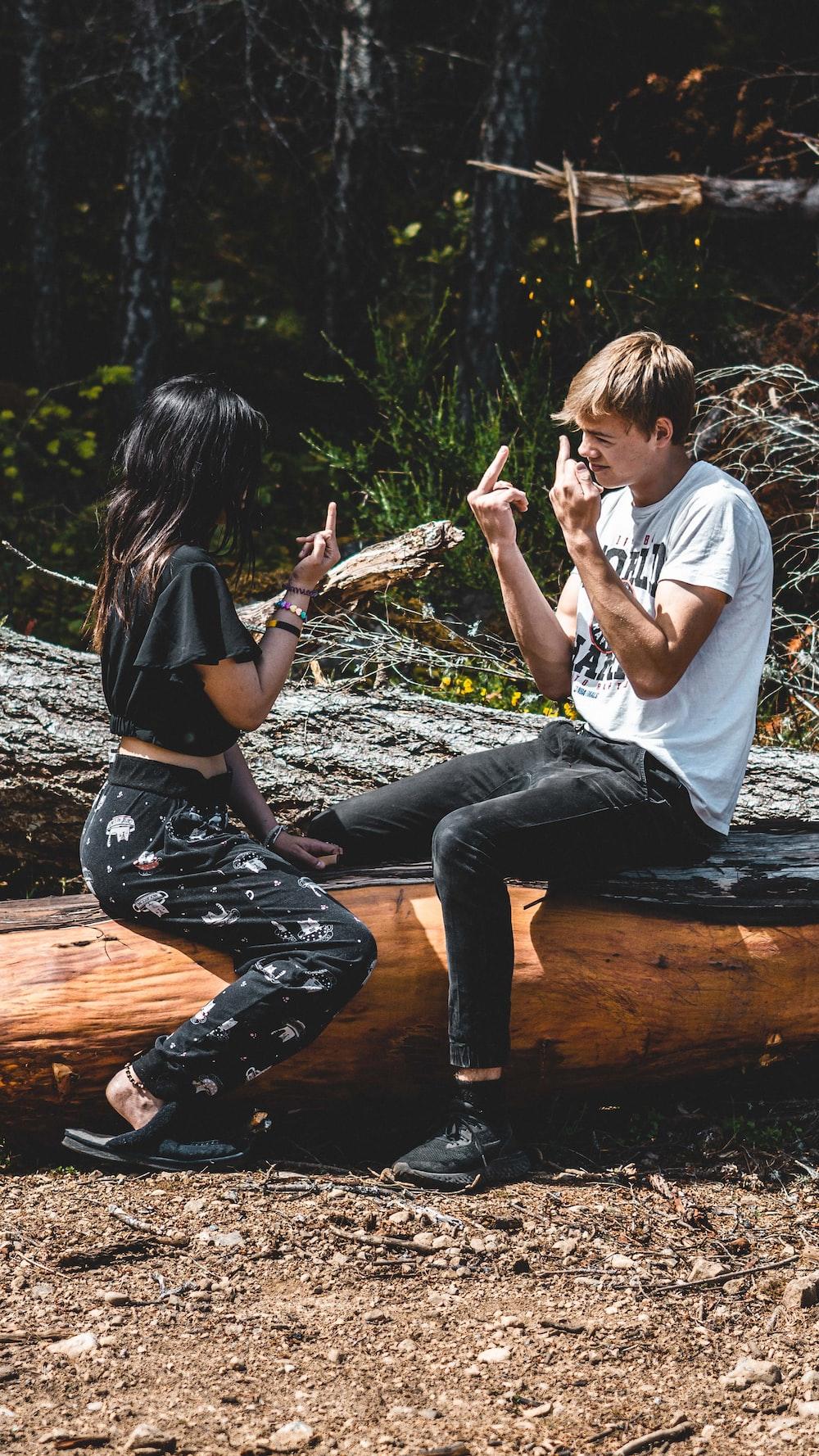 man and woman sitting on brown log